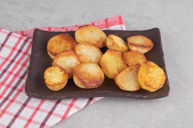 Tranches de pommes de terre frites sur plaque brune.