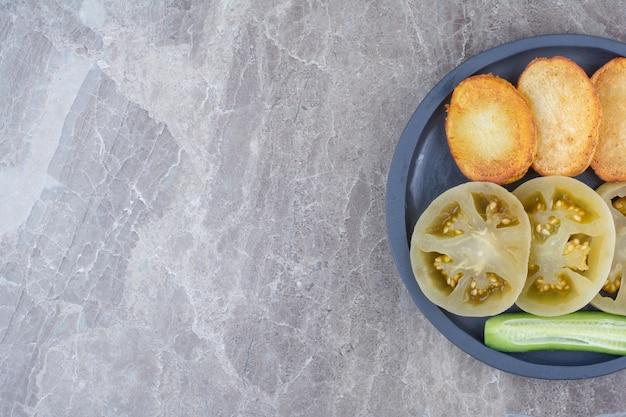 Tranches de pommes de terre frites et tomates marinées sur assiette.