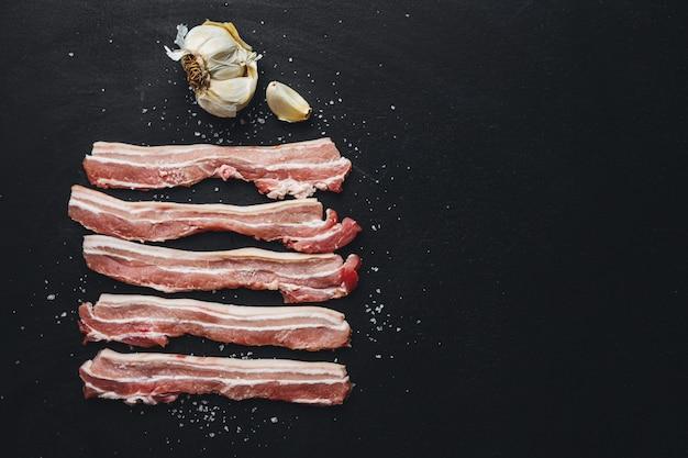 Tranches de porc cru aux épices sur noir. prêt pour la cuisson