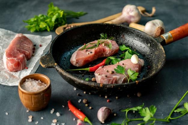 Tranches de porc cru ou steaks dans une poêle à frire chaude à la cuisine, ingrédient witj de style photo rustique