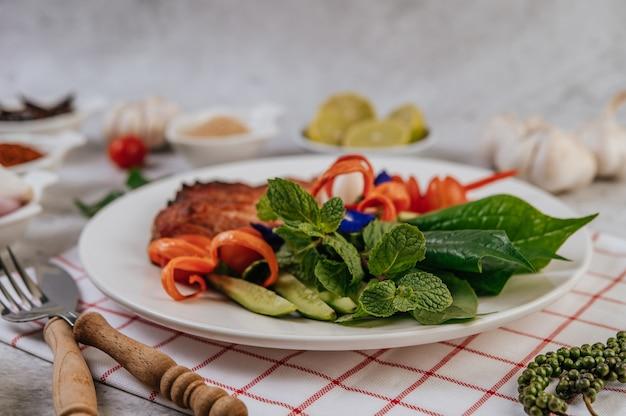 Tranches de porc frit au citron, oignon, oignon rouge, tomate, haricot long, pois papillon fleur et menthe.