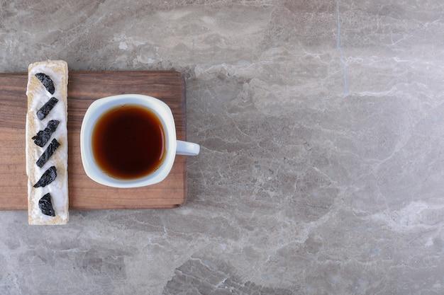 Tranches de prune sèche sur le pain croustillant et tasse de thé sur la planche de bois, sur la surface en marbre
