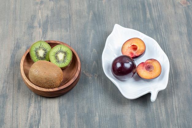 Tranches de prunes fraîches avec kiwi juteux sur une table en bois