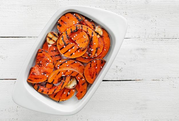 Tranches de pumpking butternut grillées sur un espace en bois blanc. aliments diététiques biologiques sains. vue de dessus, espace copie