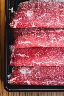 Tranches rares de bœuf japonais wagyu de catégorie a5 authentique à texture marbrée élevée pour shabu.