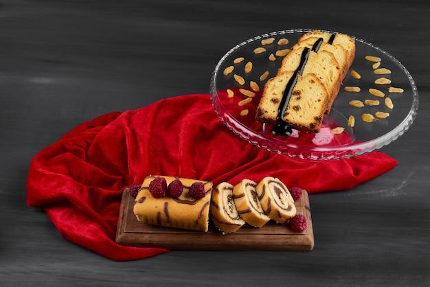 Tranches de rollcake avec des tranches de tarte sur une nappe rouge.
