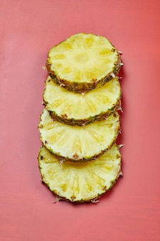 Tranches rondes d'ananas sur table rose.