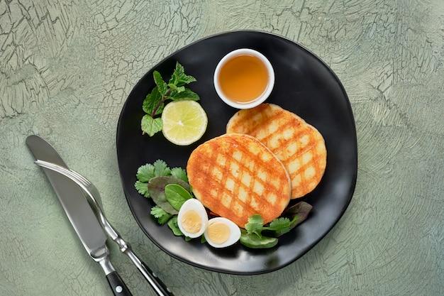 Tranches rondes grillées de fromage grec avec du miel, de la menthe fraîche et des feuilles de coriandre. mise à plat sur une table texturée verte
