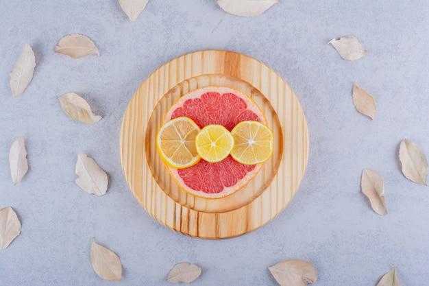 Tranches rondes de pamplemousse frais et de citrons sur une plaque en bois.