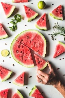 Tranches rouges de pastèque mûre avec des feuilles de menthe et des tranches de citron vert sur fond blanc. vue de dessus, pose à plat