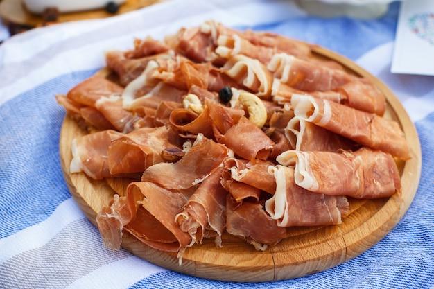 Tranches de rouleaux de jamon frais sur un plateau en bois à la couverture de pique-nique. week-end d'été
