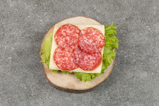 Tranches de salami sur morceau de bois avec du fromage et de la laitue