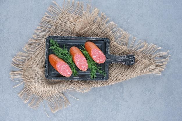 Tranches de salami sur la planche à découper noire.