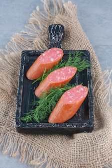 Tranches de salami de saucisse sur planche de bois avec des épices.