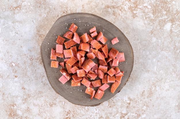 Tranches de saucisse bouillie sur une planche, sur la table en marbre.
