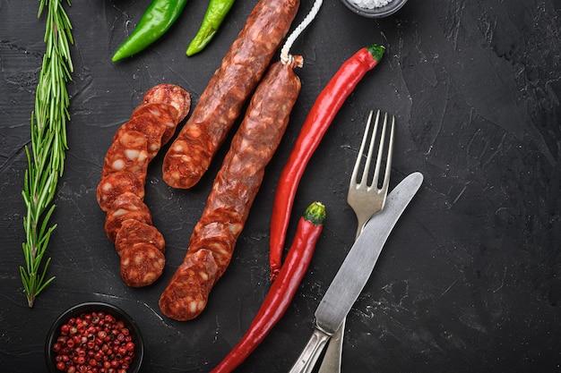 Tranches de saucisse de chorizo espagnol aux herbes et épices sur table noire, vue de dessus