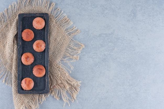 Tranches de saucisse frite sur plaque en bois noir.