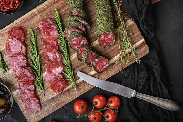 Tranches de saucisse de salami fuet espagnol sur table noire, mise à plat.