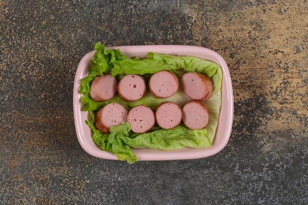 Tranches de saucisses grillées dans un bol rose.