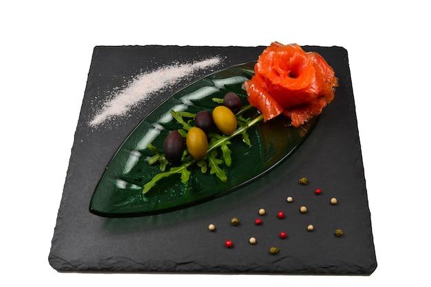 Tranches de saumon sur une assiette avec du sel et des olives isolées sur blanc.