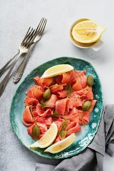 Tranches de saumon légèrement salé aux câpres, citron et aneth sur une plaque en céramique sur une table en béton gris. vue de dessus.