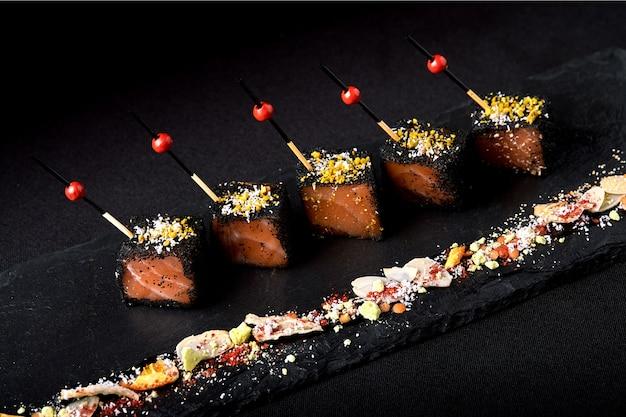 Tranches de saumon mariné dans une panure noire, avec des brochettes disposées sur une plaque noire.