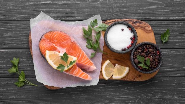 Tranches de saumon rouge cru sur planche de bois