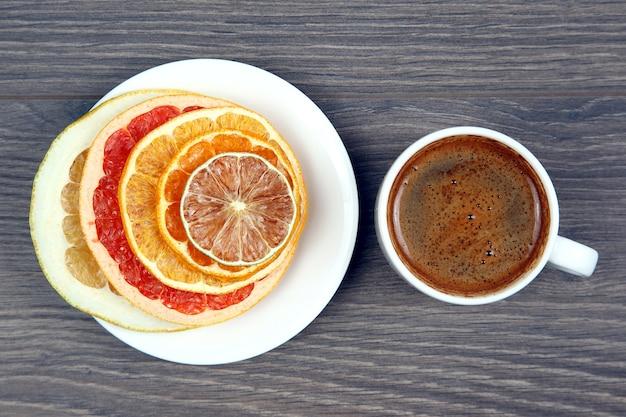 Tranches séchées de divers agrumes et café noir dans une tasse blanche