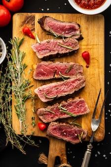Tranches de steak de boeuf sur une fourchette à viande sur une planche à découper en bois.