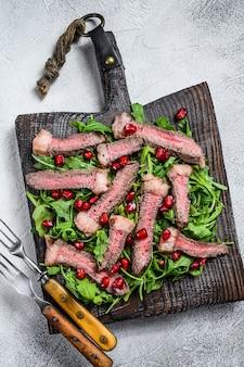 Tranches de steak de boeuf grillé avec salade de feuilles de roquette sur une planche à découper rustique. fond blanc. vue de dessus.