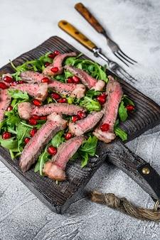 Tranches de steak de boeuf grillé avec salade de feuilles de roquette sur une planche à découper rustique.