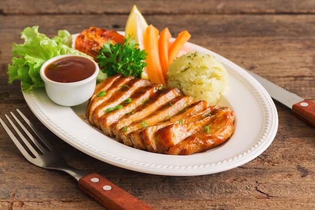 Tranches de steak de porc barbecue sur une plaque blanche. steak de porc délicieux pour le déjeuner ou le dîner