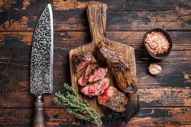 Tranches de steaks grillés sur une planche de bois sur une table en bois. vue de dessus.