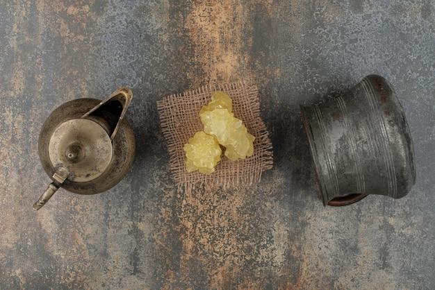 Tranches de sucre jaune avec deux bouilloires anciennes sur mur de marbre