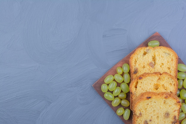 Tranches de tarte aux raisins verts sur un plateau en bois.