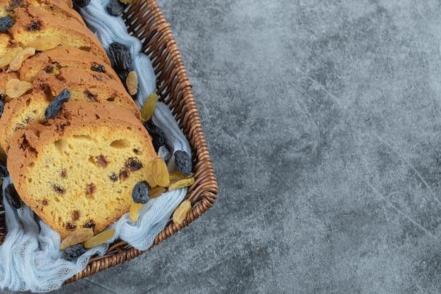 Tranches de tarte aux sultanes classiques sur panier en bois sur serviette bleue.