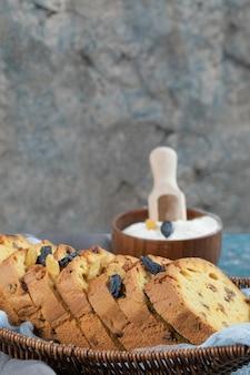 Tranches de tarte sultana sur panier en bois sur serviette bleue.