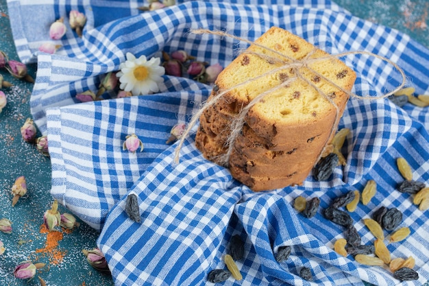 Tranches de tarte sultana sur serviette à carreaux bleu.