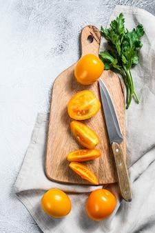 Tranches de tomates cerises jaunes fraîches sur une planche à découper
