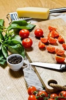 Tranches de tomates cerises sur une planche à découper en bois.