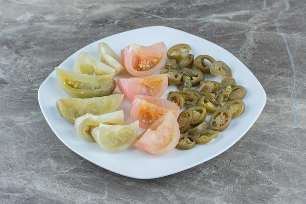 Tranches de tomates et de poivrons marinés sur une plaque en céramique blanche.