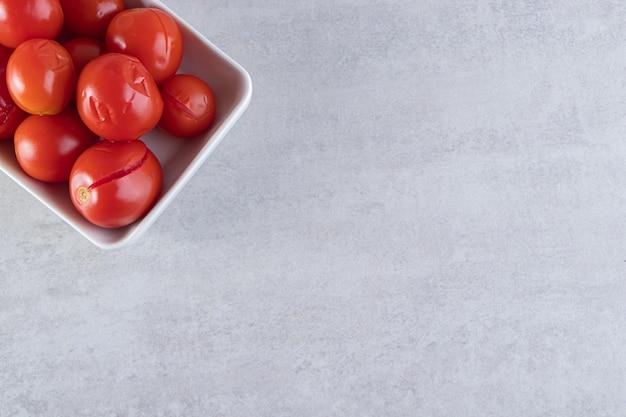 Tranches de tomates salées dans un bol en bois placé sur fond de pierre.