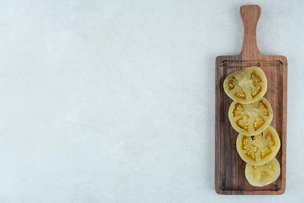 Tranches de tomates vertes marinées sur planche de bois.
