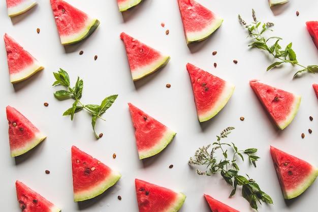 Tranches de tranches triangulaires de pastèque rouge mûre avec graines avec feuilles de menthe verte, citron vert