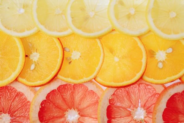 Tranches translucides de citron, orange et pamplemousse sur fond blanc, tranches d'agrumes, mélange d'été
