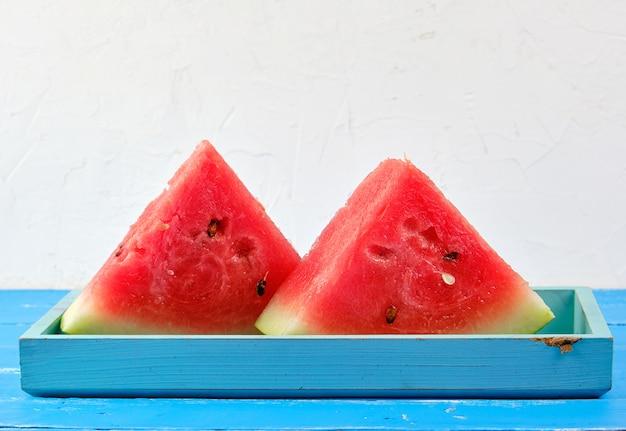 Tranches de triangles mûres de pastèque ronde rouge avec des graines