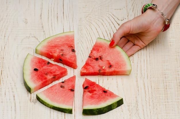 Tranches triangulaires de melon d'eau couché sur un cercle une main féminine prend une tranche, bois clair