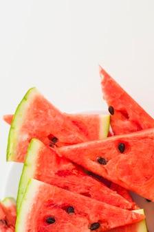 Tranches triangulaires de melon d'eau sur fond blanc