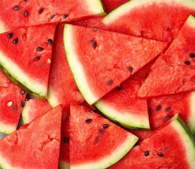 Tranches triangulaires tranchées de melon d'eau rouge mûr avec des graines