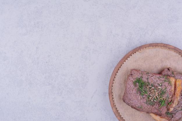 Tranches de viande de bifteck aux herbes et épices sur une planche de bois.